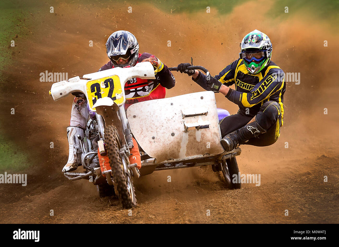 A scramble bike with side-car, rider and passanger, at speed raising a dramatic cloud of dust and heading straight - Stock Image