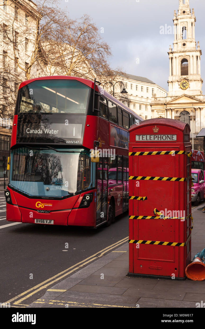 London street with a decommissioned phone box and a double decker bus - Stock Image