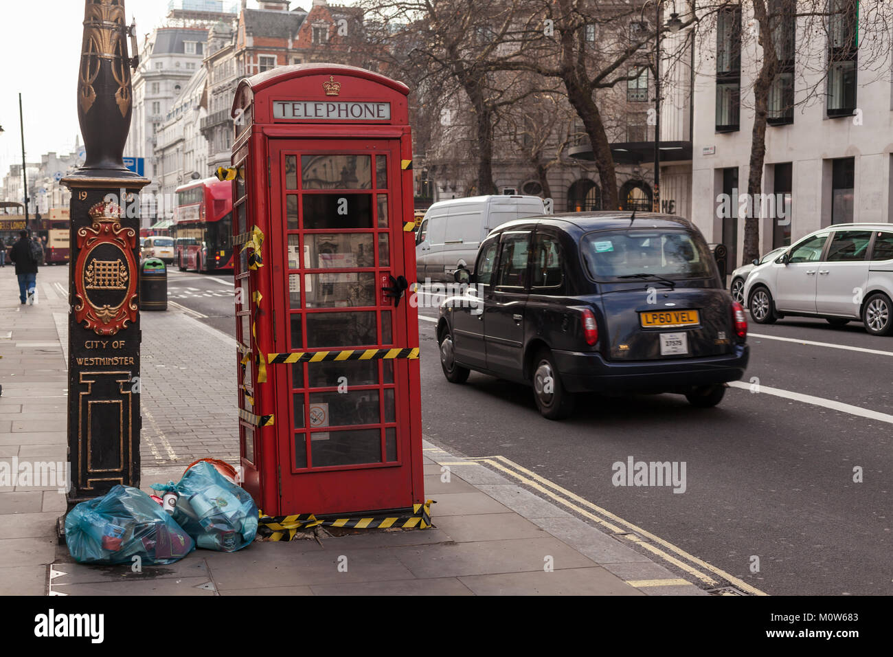 London street with a decommissioned phone box and a black London taxi - Stock Image