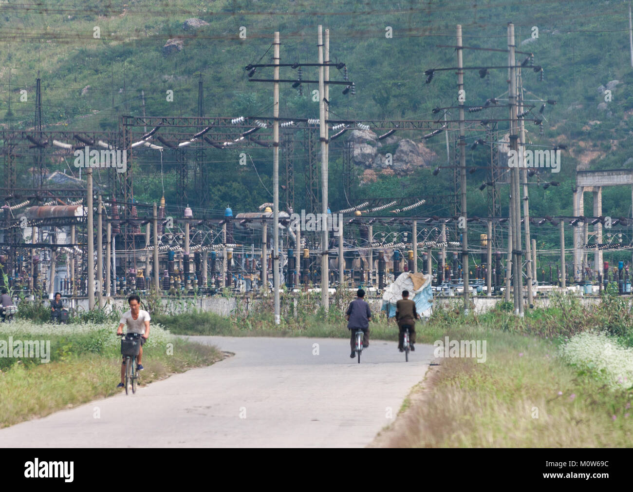 North Korean men riding in font of a power station, North