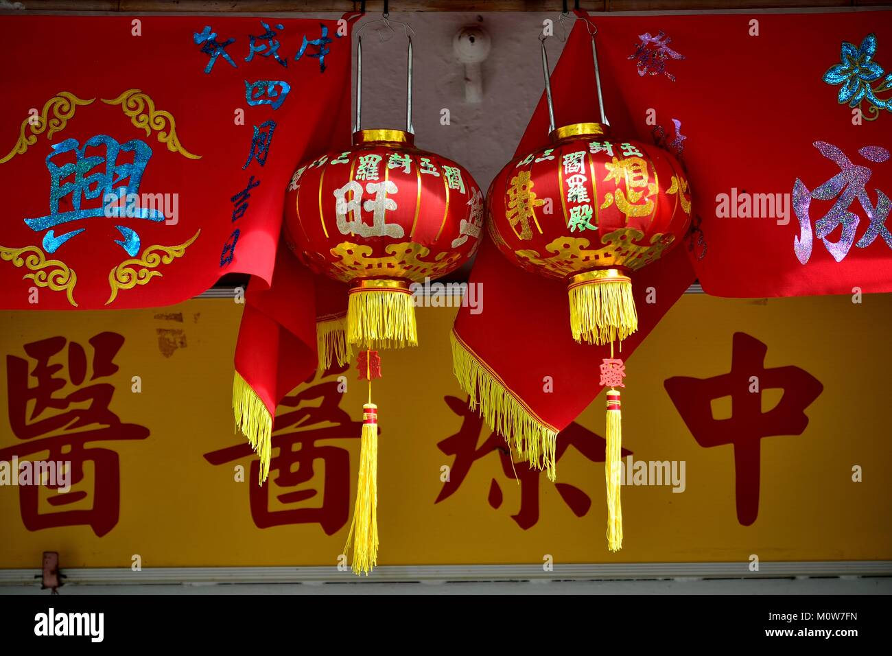 Red and gold lanterns with banners celebrating Chinese Lunar New Year in Geylang, Singapore - Stock Image