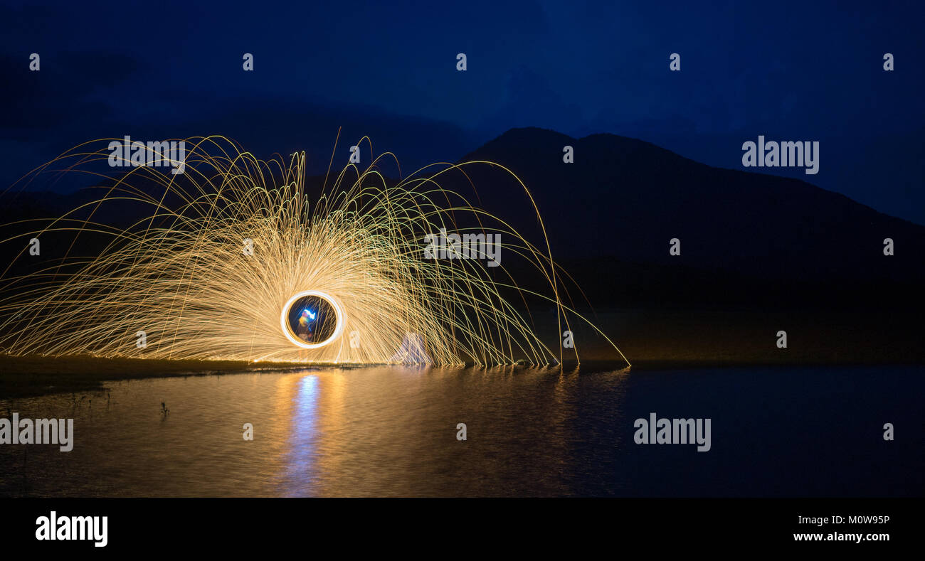 Ring of fire on the lake at night with mountain background. - Stock Image