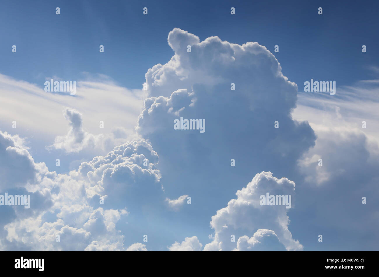 The blue sky with the cumulus clouds lit with the sun. - Stock Image