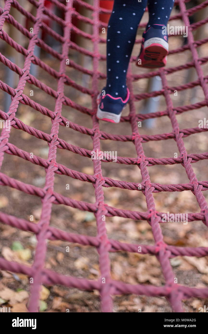 Children playing with rope climbing equipment in the playground in Battersea Park, London - Stock Image