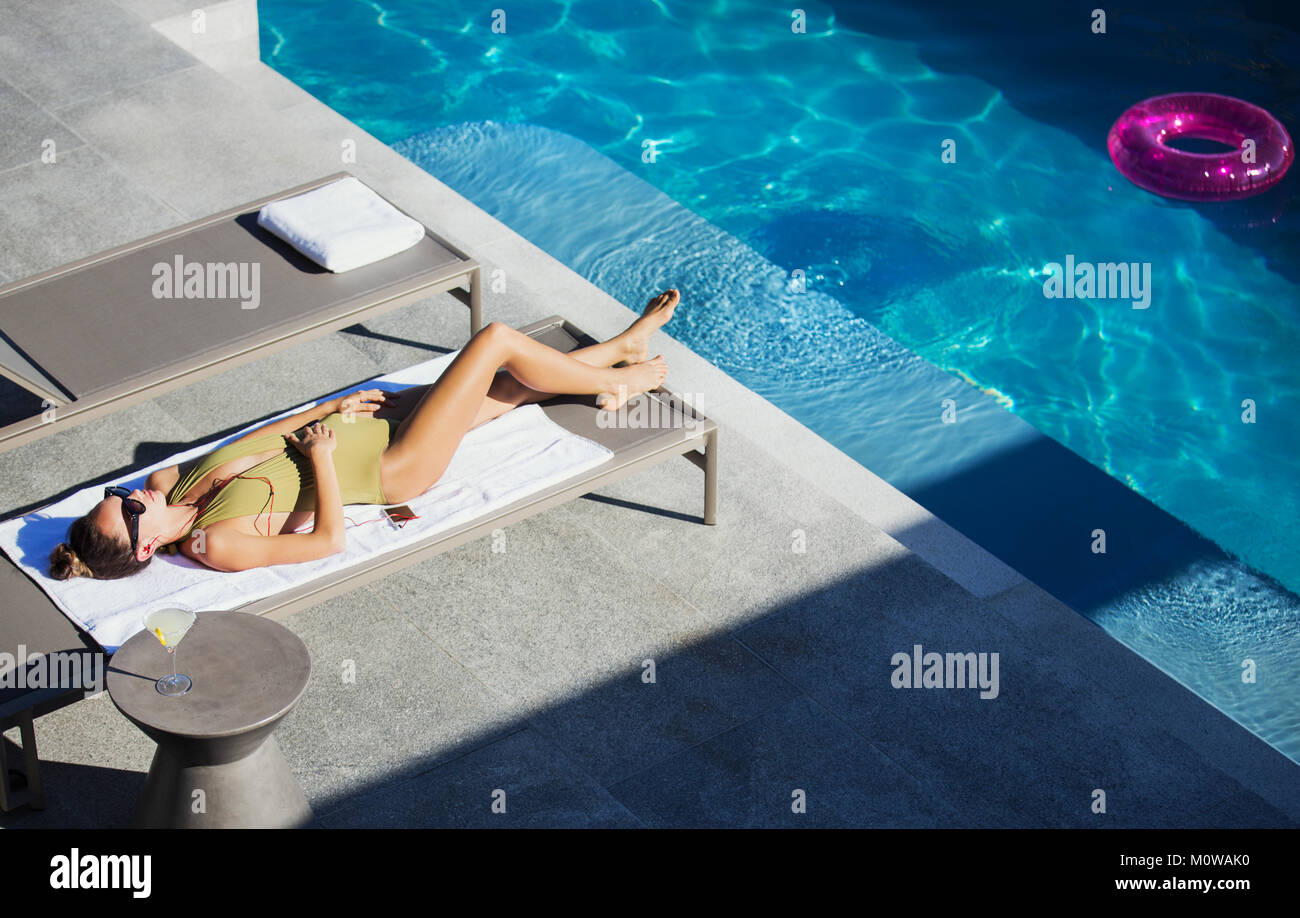 Woman in bathing suit sunbathing on lounge chair at sunny luxury ...