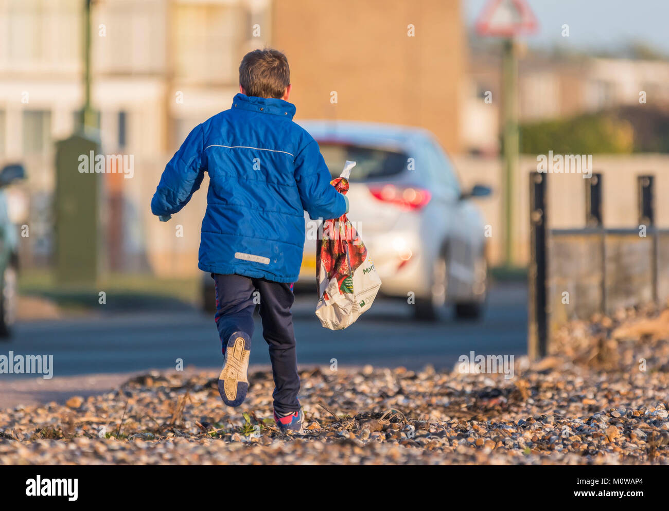Young boy running away. Escaping concept. Child on the run. - Stock Image
