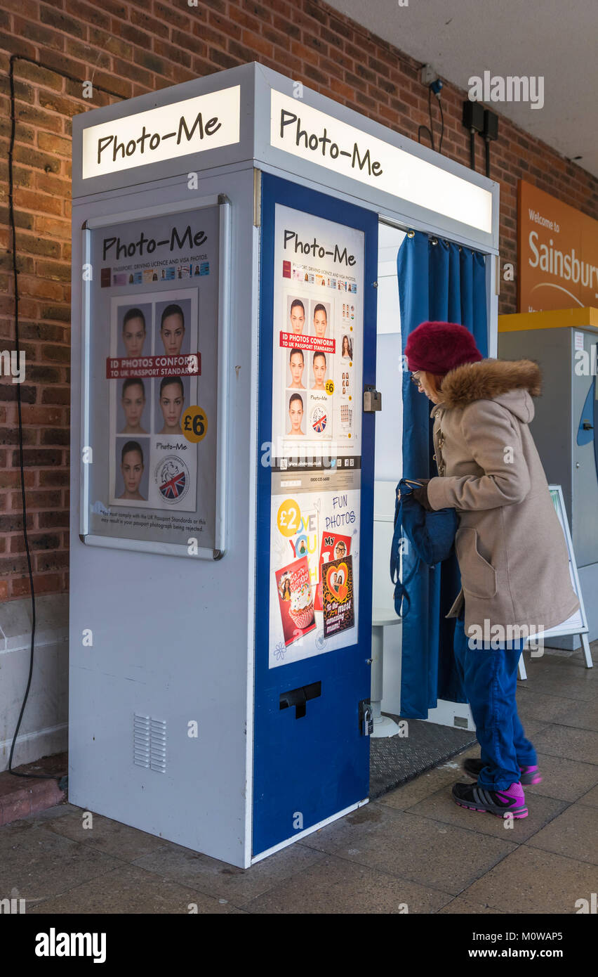 Woman walking into a Photo-Me passport photo booth in the UK. - Stock Image