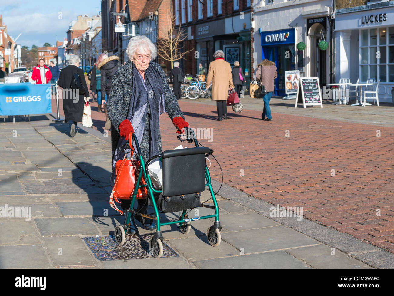 Elderly woman with wheeled rollator (wheeled zimmer frame walking aid) in a pedestrianise shopping area in Chichester, - Stock Image