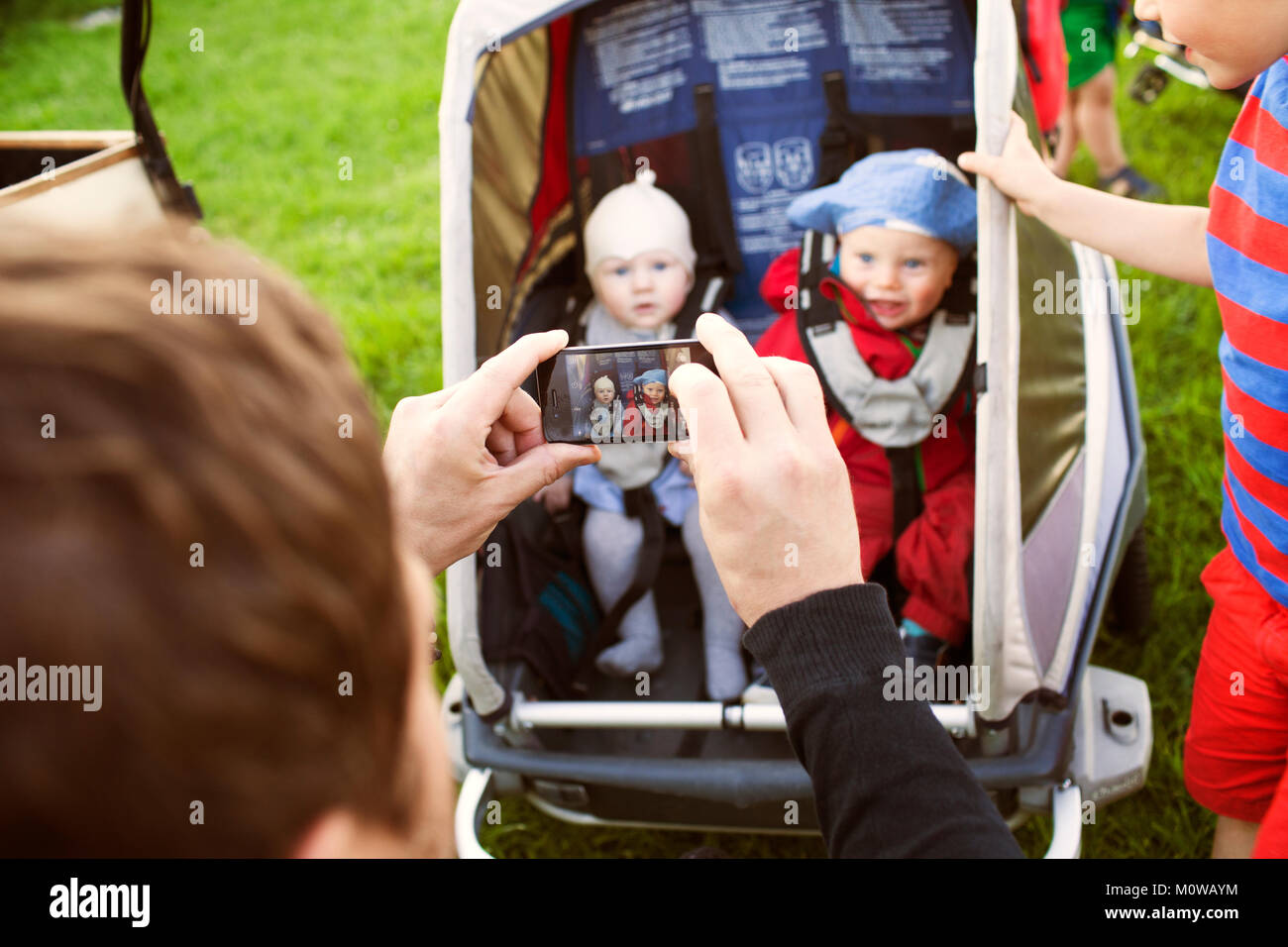 Father taking photograph of babies - Stock Image