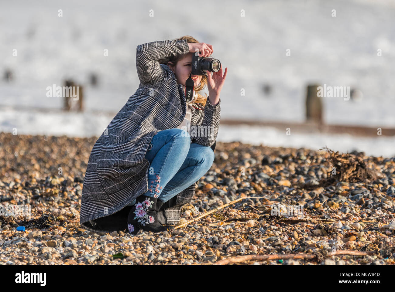 Young woman female photographer crouched down taking photos on a beach. - Stock Image