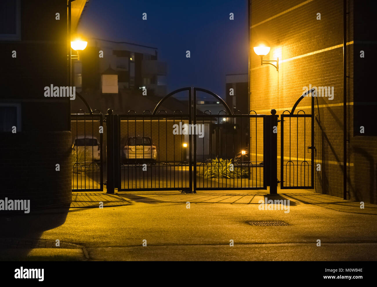 Gates and movement sensitive security lights at the entrance to a private car park in the UK. - Stock Image