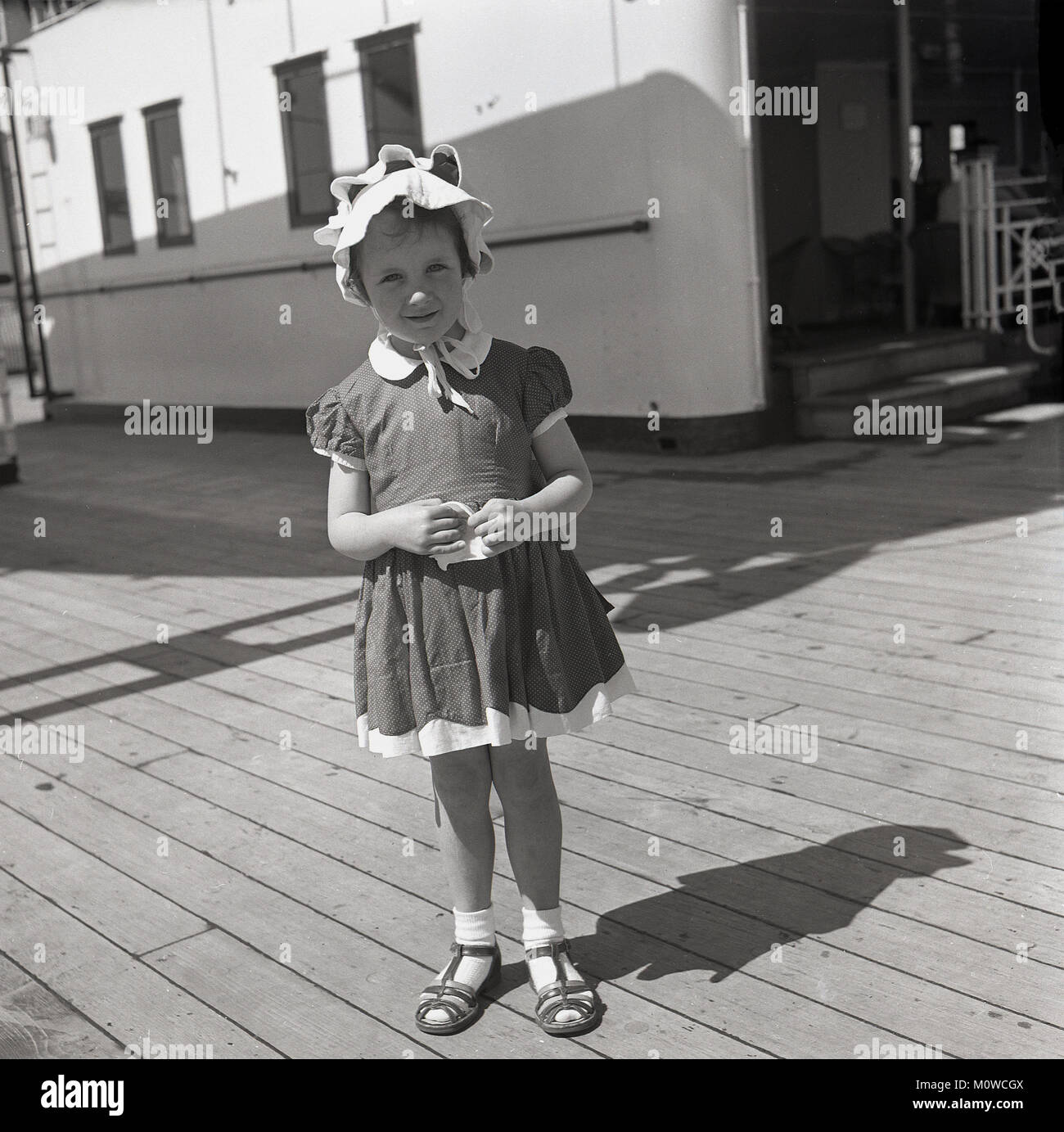 1950s, historical picture of a young girl wearing a pretty dress and bonnet standing on the deck of a Union-Castle - Stock Image