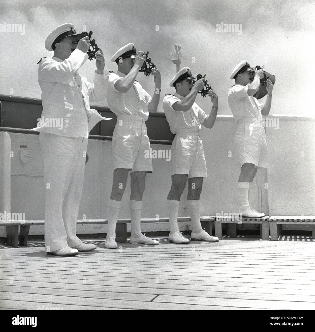 1950s, historical, four male officers in uniform standing on the deck of a Union-castle cargo and passenger steamship - Stock Image