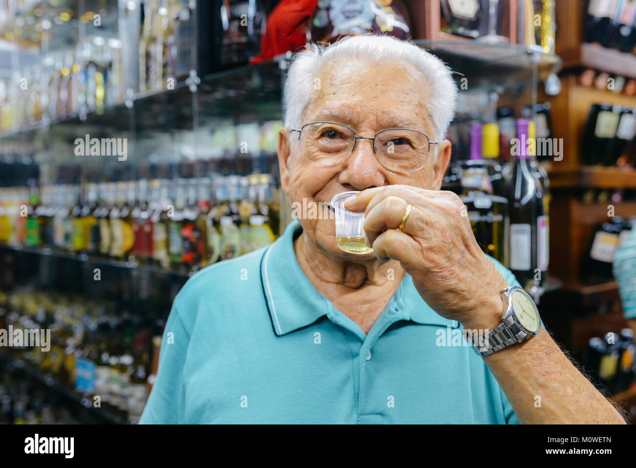 Model Released: Older man 80-90 samples a type of cachaca drink, made from distilled sugar cane, Mercado Central - Stock Image