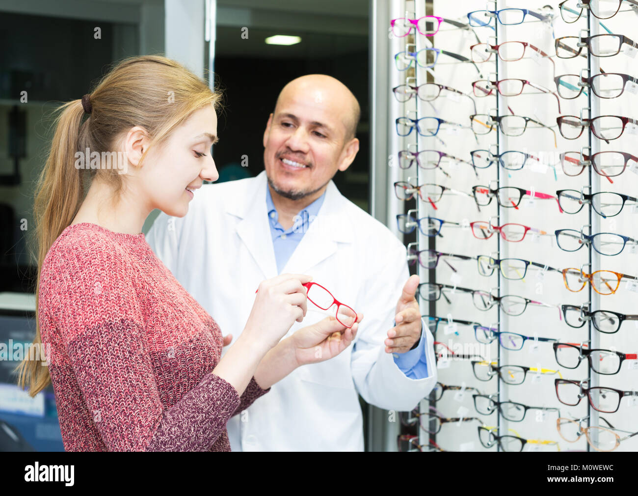 Senior male optician offering glasses frames to positive young woman ...