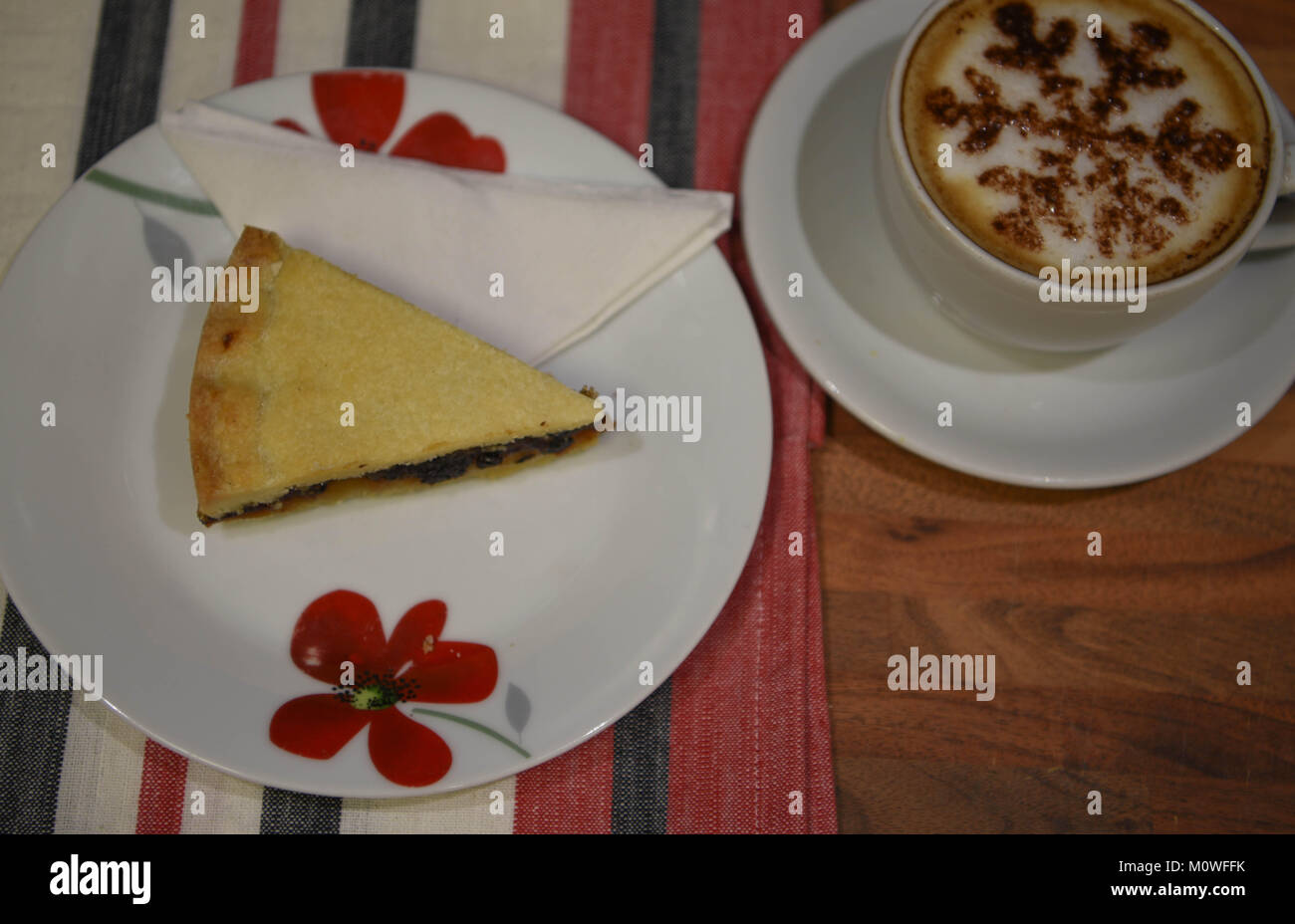 food photography with a home made pastry and current fruit slice of English Eccles tart on a red and white floral - Stock Image