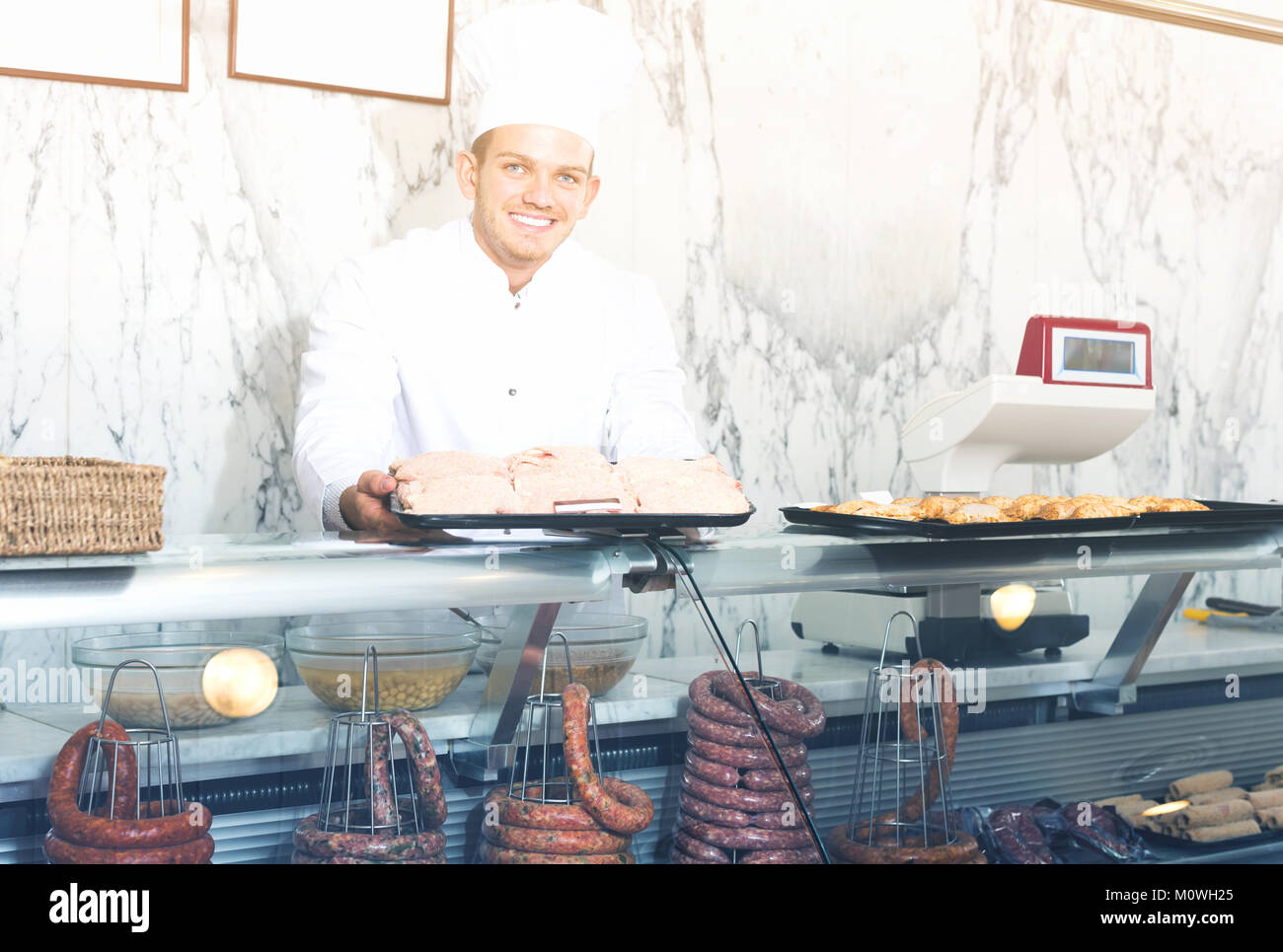 professional young seller at butcher store offering fresh products Stock Photo