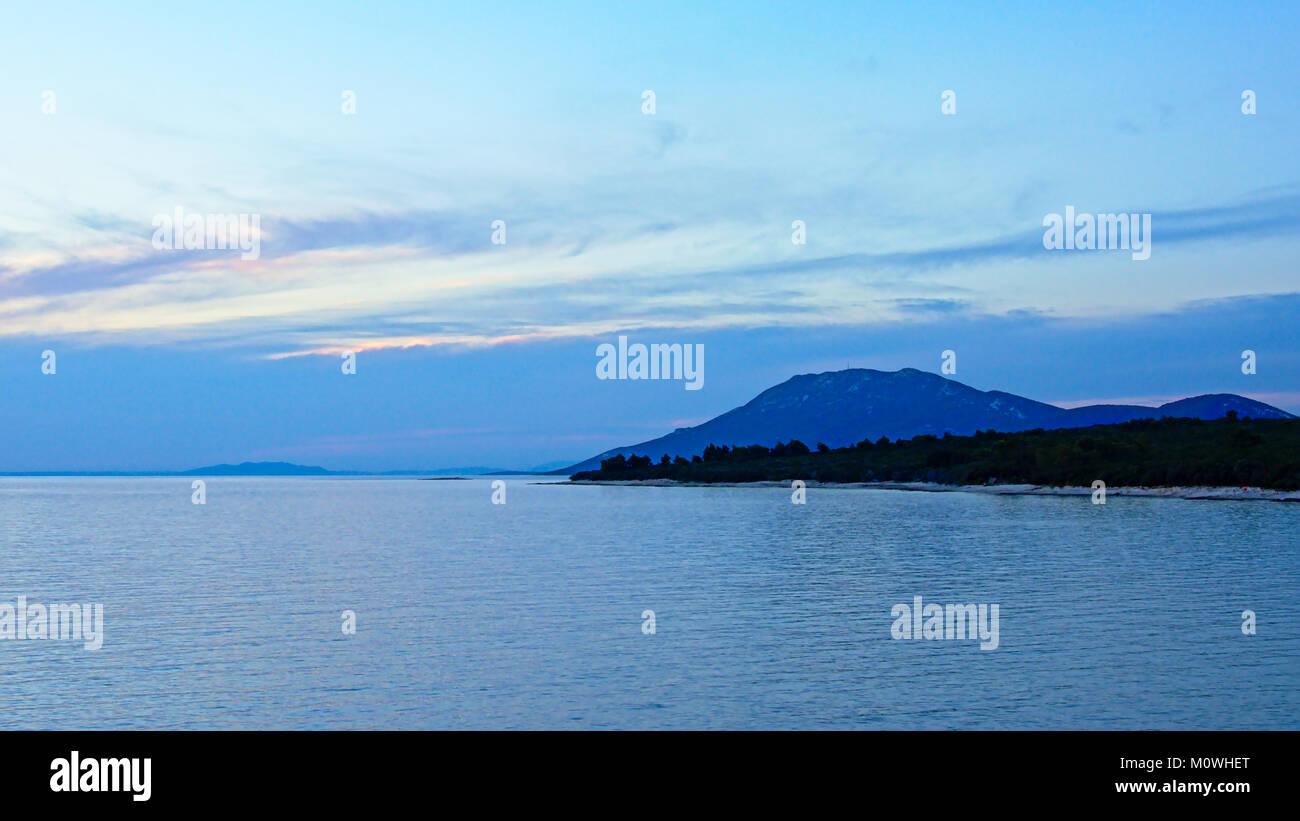 Blue cloudy sky with some orange over te Adriatic sea just after sunset, with island with trees and mountain in Stock Photo