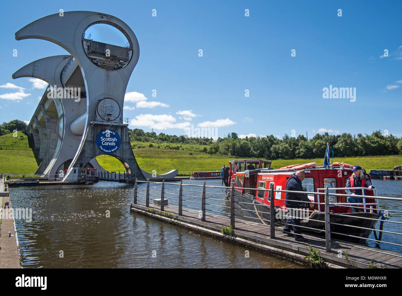 Canal boat with tourists mooring at Falkirk Wheel, rotating boat lift, Stirlingshire, Scotland, UK - Stock Image
