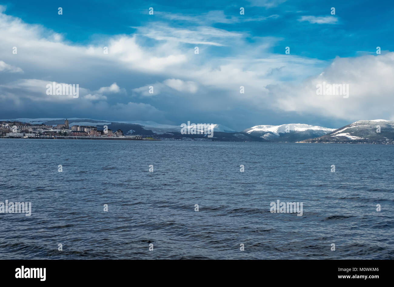 The town of Gourock in Inverclyde Scotland looking out over the Bay to the snow covered hills and Gareloch beyond. - Stock Image