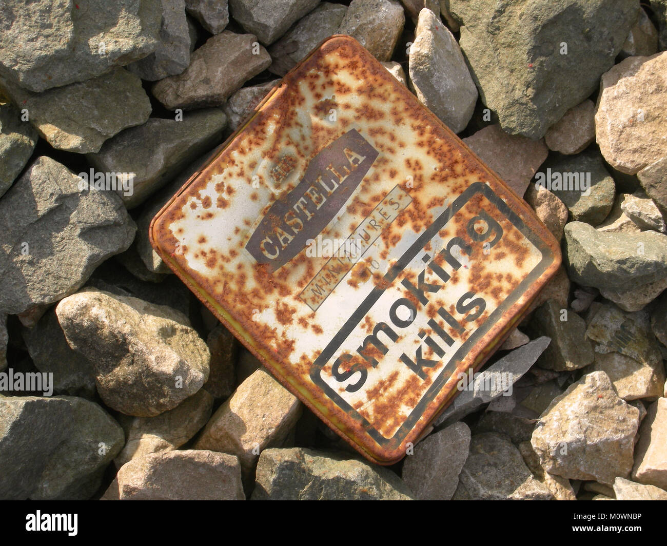 Rusty tin can for miniature cigars thrown away - Stock Image