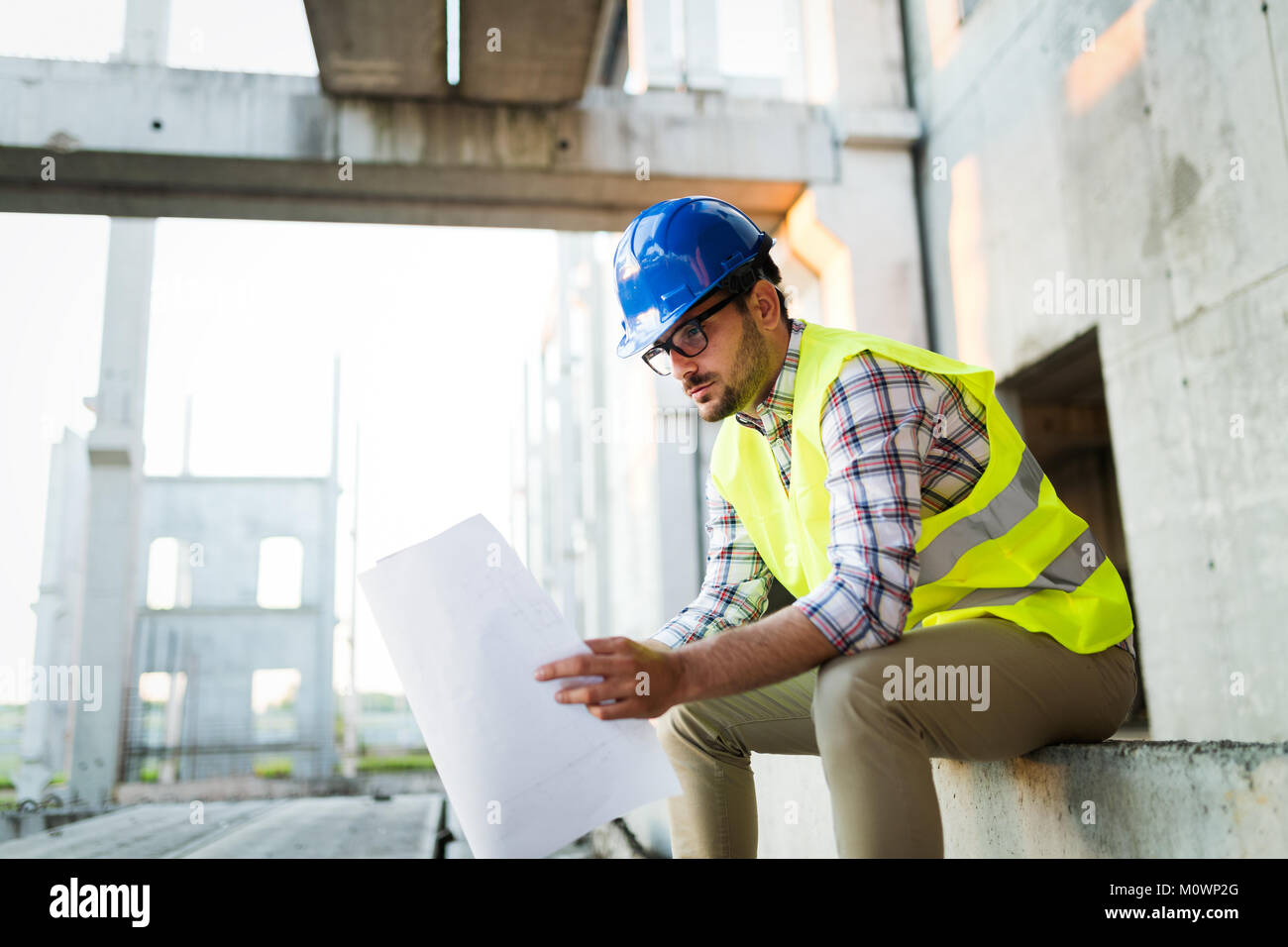 Picture of construction site engineer looking at plan - Stock Image