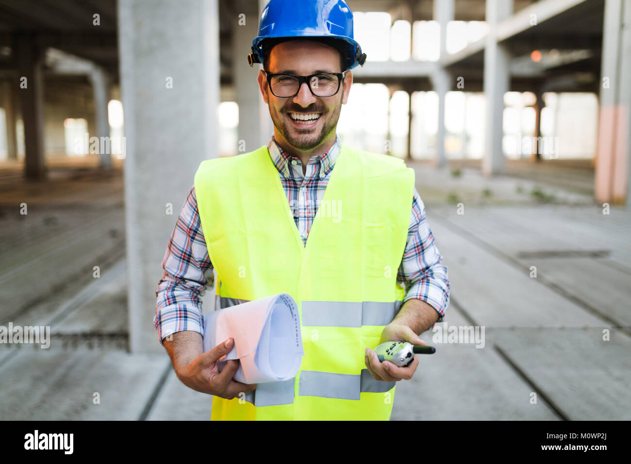 Male architect with blueprints using walkie-talkie Stock Photo
