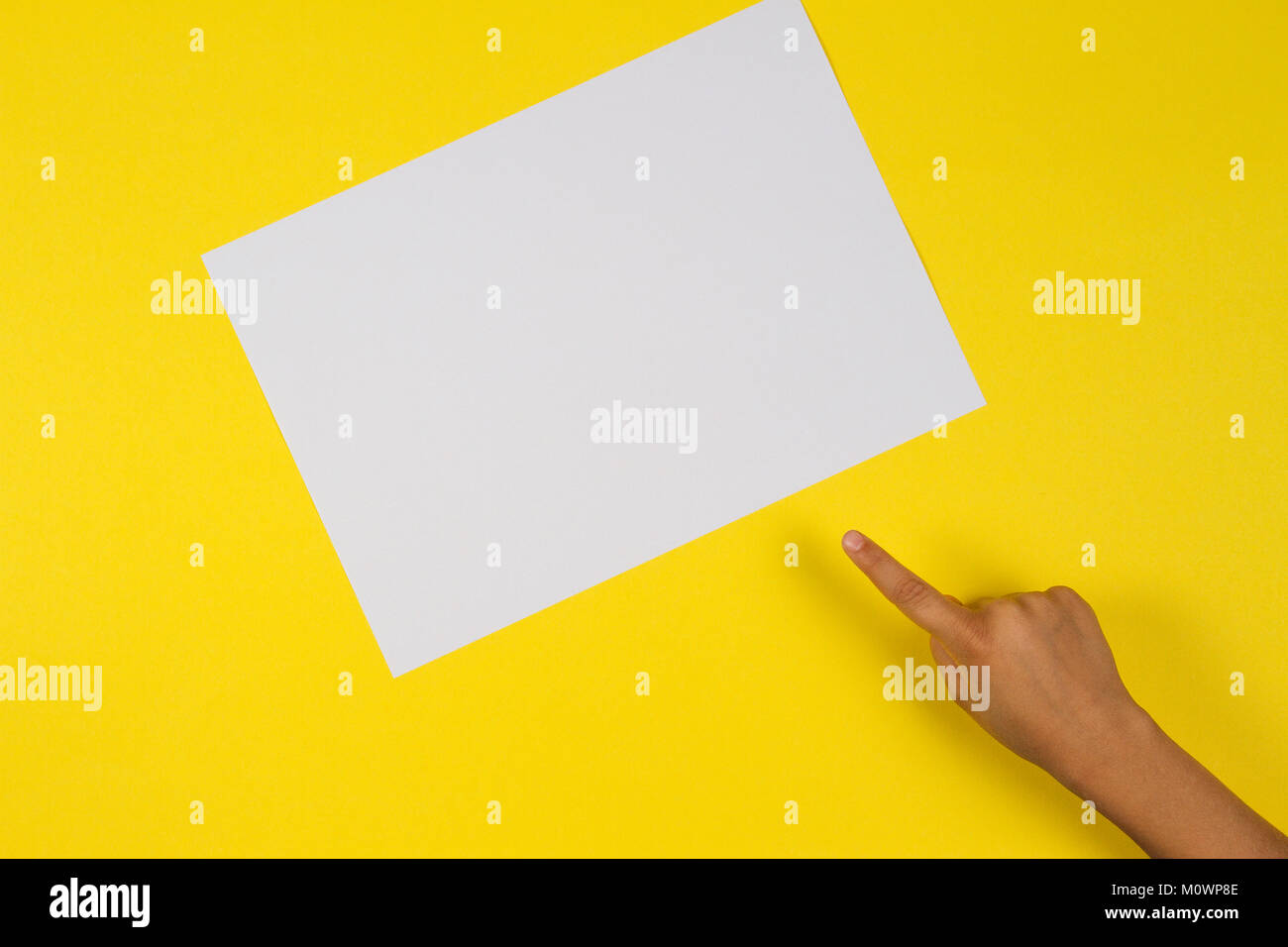 Kids hand finger pointing to white blank paper card on yellow background - Stock Image
