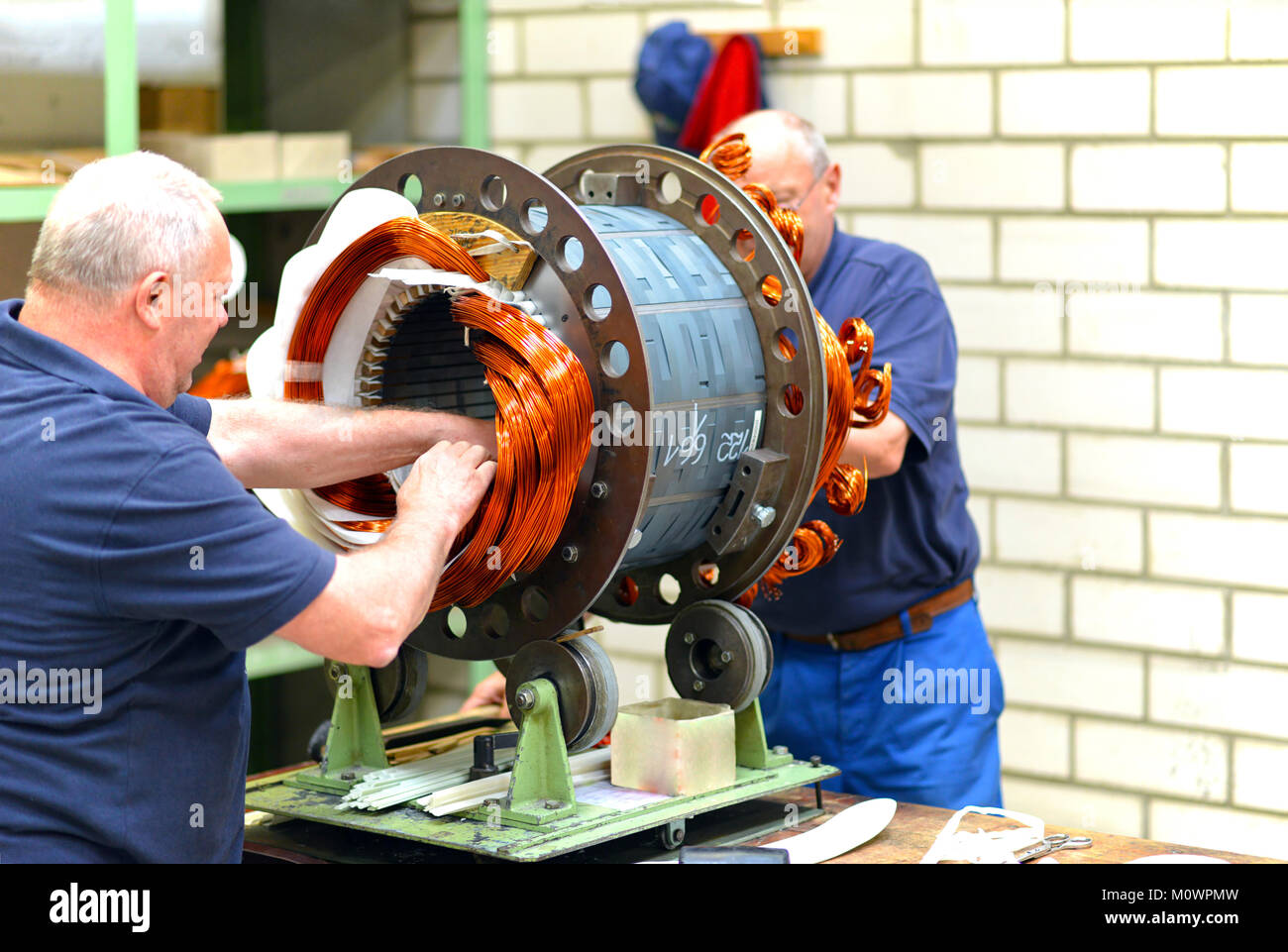 Workers in a factory assemble electric motors - Stock Image