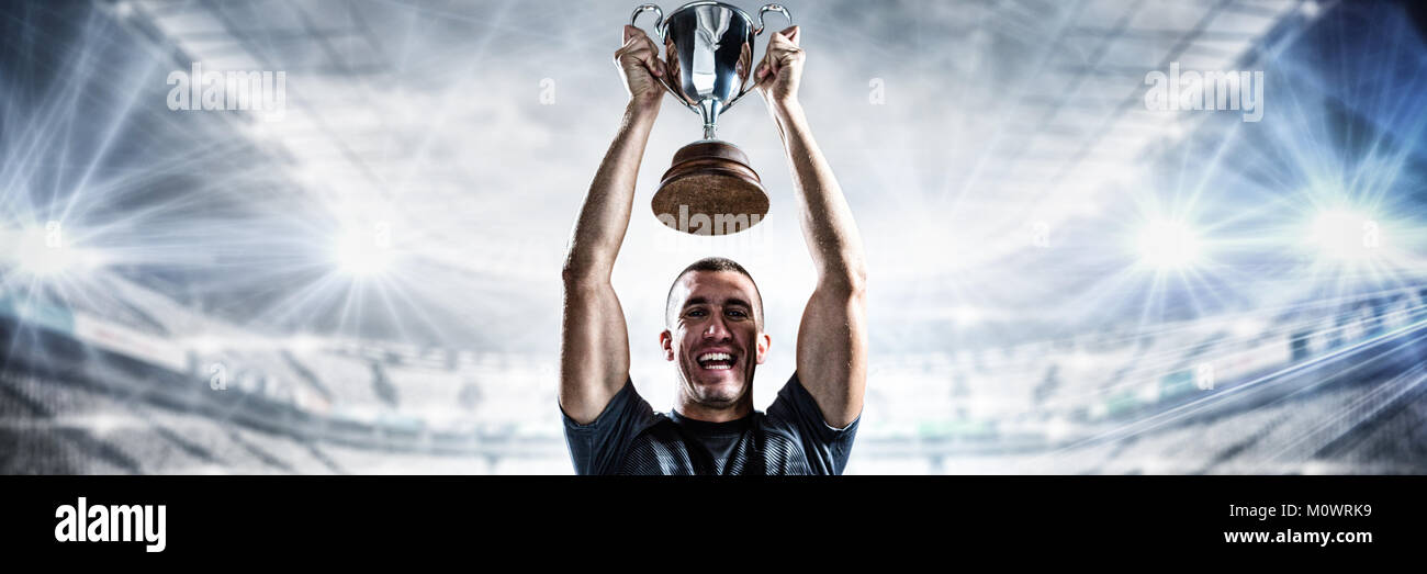 Composite image of portrait of successful rugby player holding