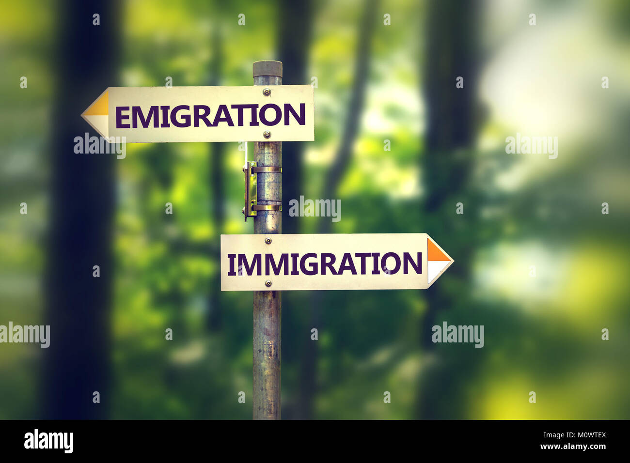 Pole with guiding tablets offering choice between emigration and migration. - Stock Image