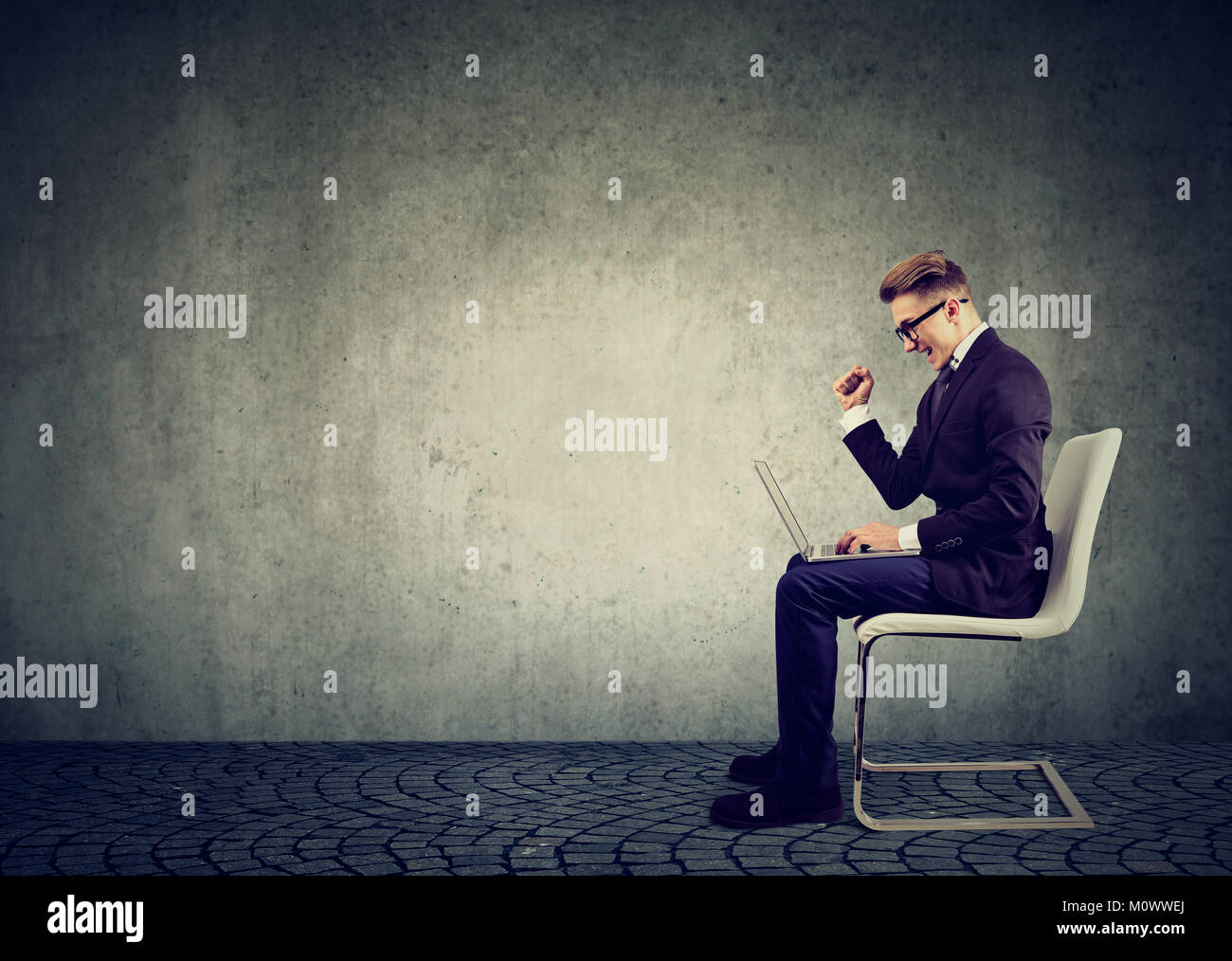 Young businessman watching laptop with excitement having good news about job. - Stock Image