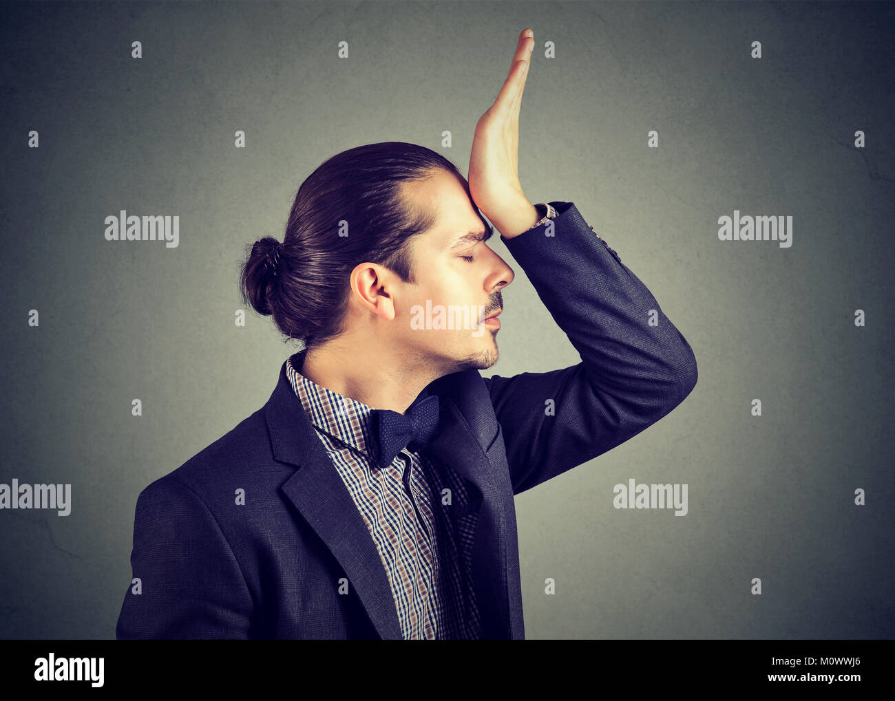 Young elegant man slapping forehead upset with foolish mistake while posing on gray. - Stock Image