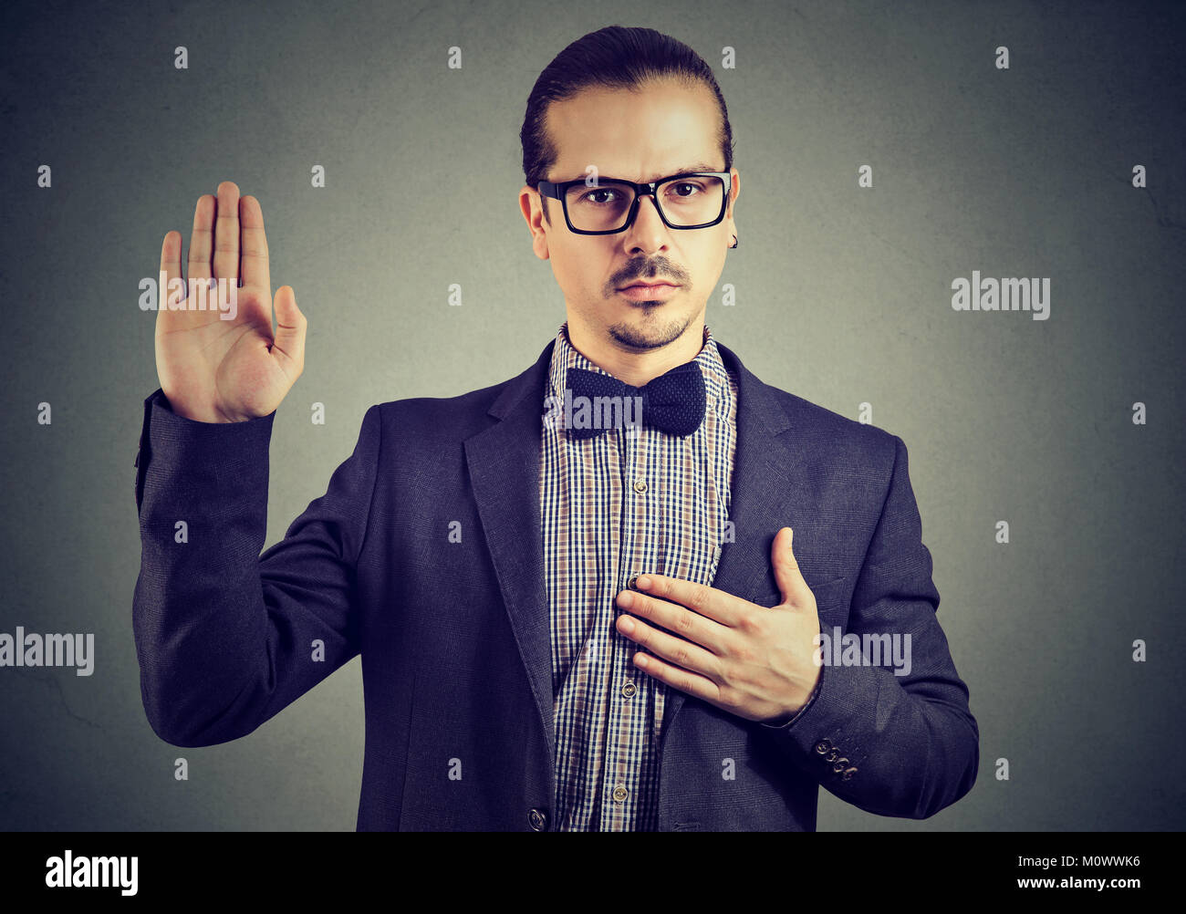 Young man in formal clothing and eyeglasses swearing in being trustworthy while looking at camera. - Stock Image