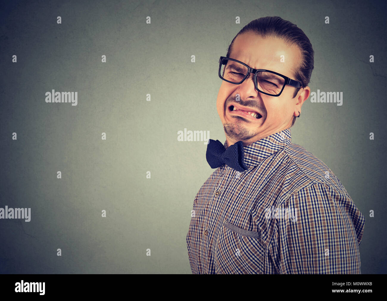 Man in eyeglasses and formal clothing grimacing with disgust on gray background. Stock Photo