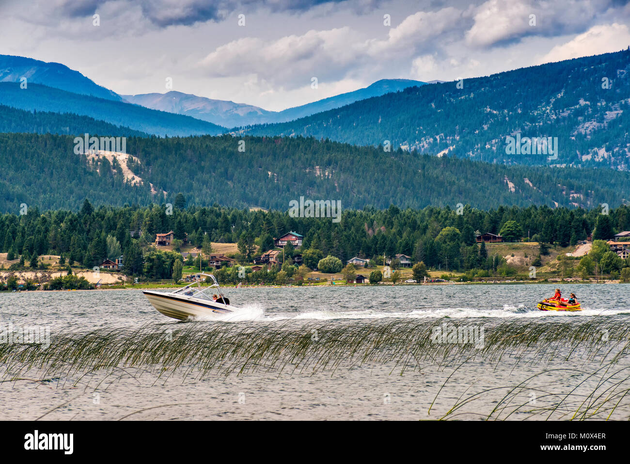 Speedboat pulling woman and young girl in rubber boat, Lake Windermere, Columbia Valley, Purcell Mountains, near - Stock Image