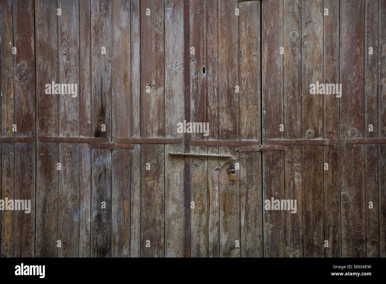 Wooden brown door. Weathered blank, banner, background with rusty latch and padlock. Closeup, detail Stock Photo