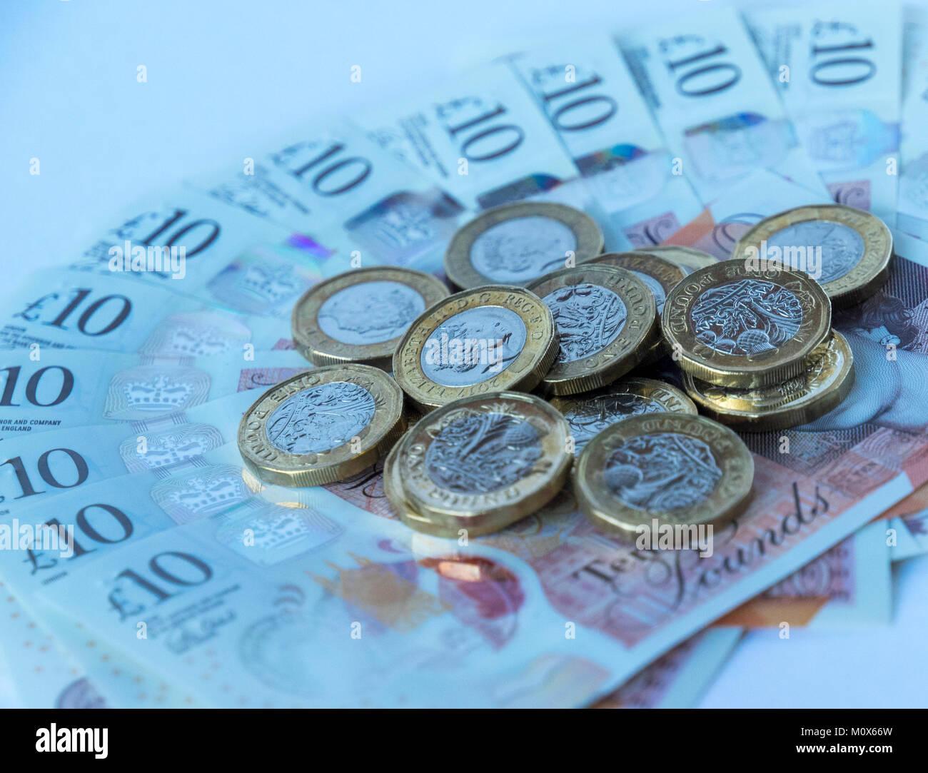 Several new British pound coins lying randomly on a fanned out bed of new polymer ten pound sterling notes - Stock Image