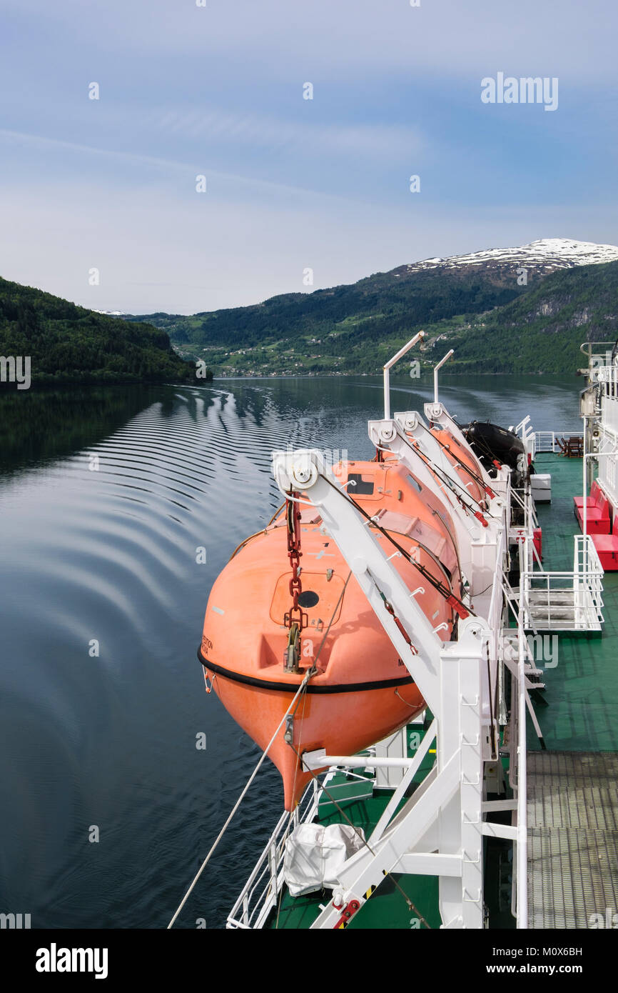 Enclosed lifeboat hanging from davits on side of MS Expedition cruise ship sailing in a fjord. Sogn og Fjordane, Stock Photo