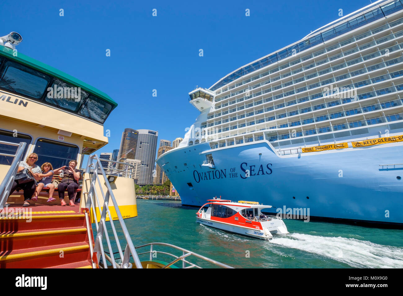 Sydney Ferry ride from Circular Quay. Passing Royal Caribbean's Ovation of the Seas cruise ship moored at Overseas - Stock Image