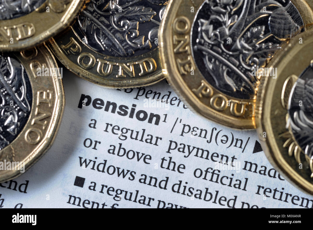 DICTIONARY SPELLING OF WORD 'PENSION' WITH ONE POUND COINS RE RETIREMENT PENSIONS INCOMES SAVINGS OLD AGE - Stock Image