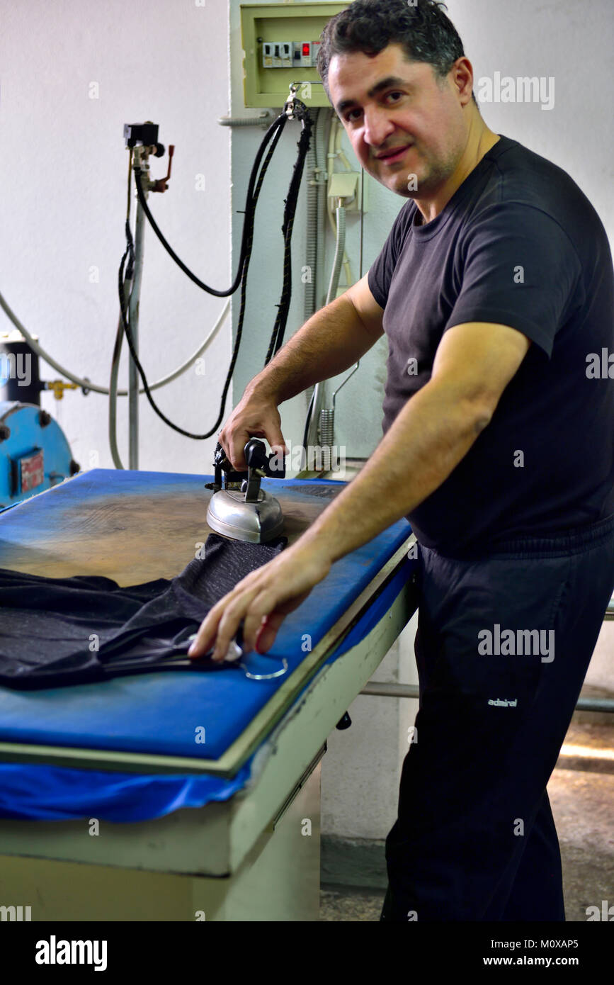 Man ironing in commercial laundry, Athens, Greece - Stock Image