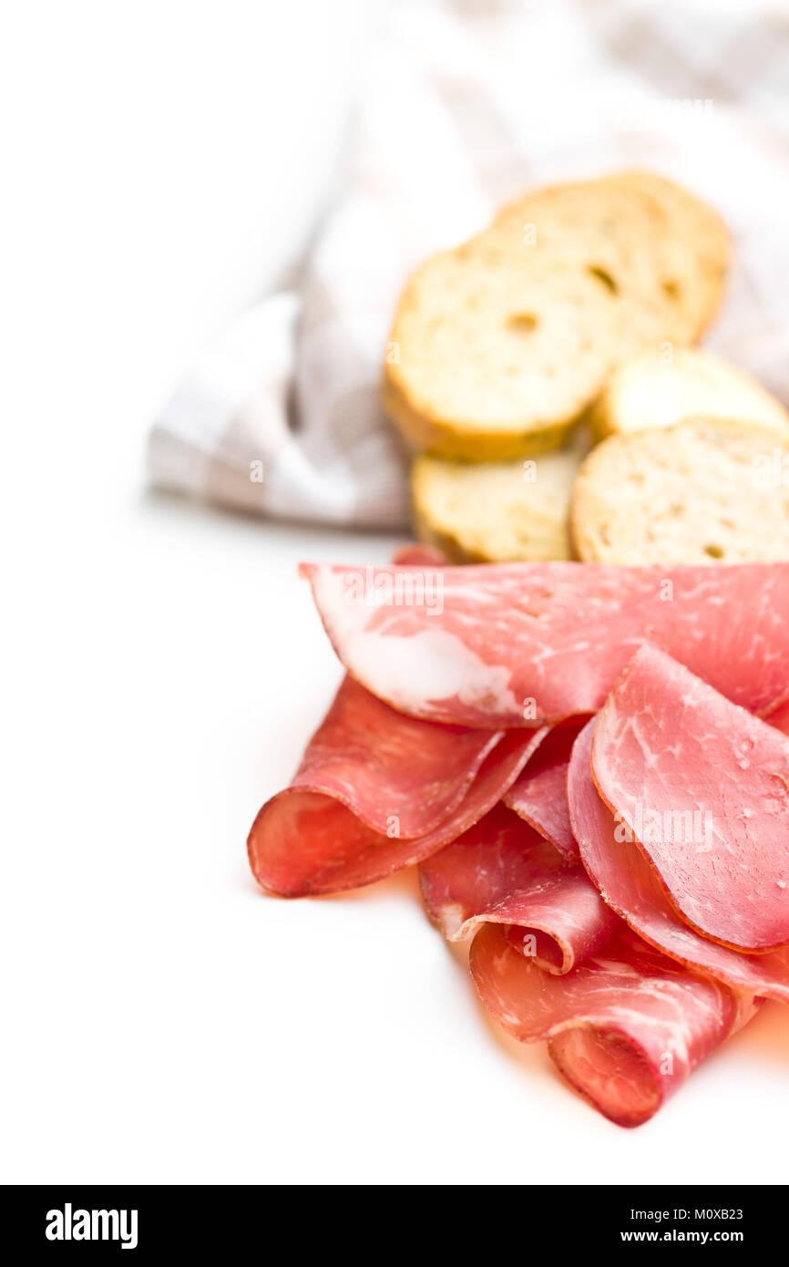 Sliced prosciutto crudo isolated on white background. - Stock Image