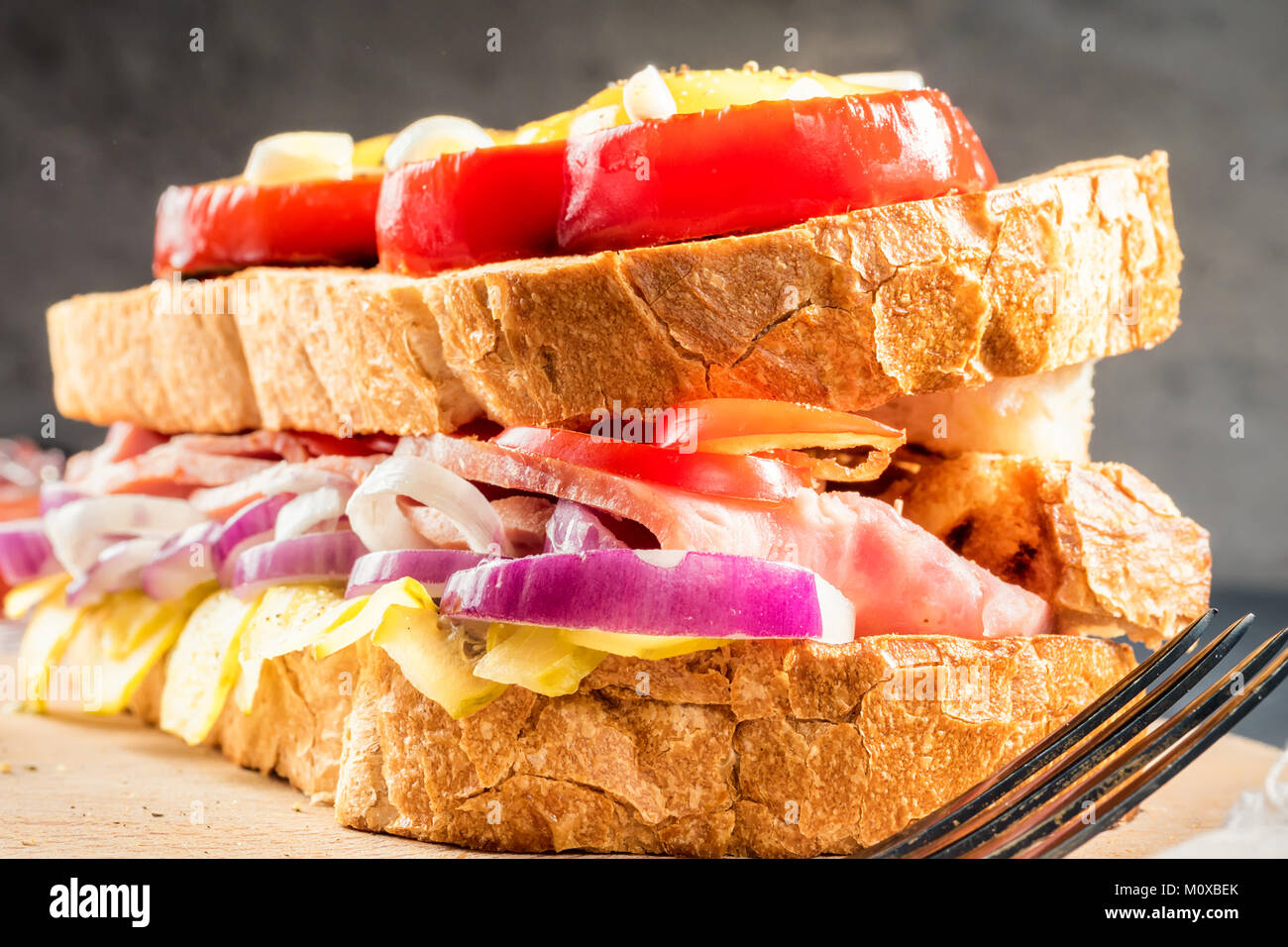 Fried egg fried in slice of red sweet pepper and sandwich with ham and seasonal vegetables on white plate. Food - Stock Image