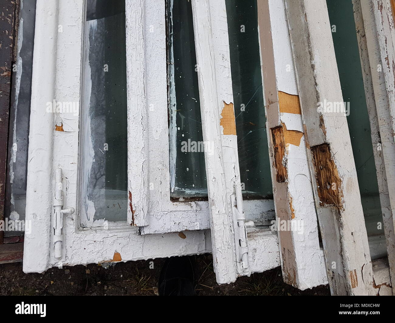 Old wooden window frames with white falling paint, stand in a row ...