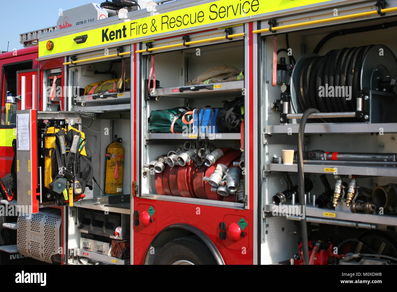 CLOSE UP VIEW OF KENT FIRE & RESCUE SERVICE FIRE TRUCK WITH COMPARTMENTS OPEN SHOWING FIREFIGHTING EQUIPMENT - Stock Image
