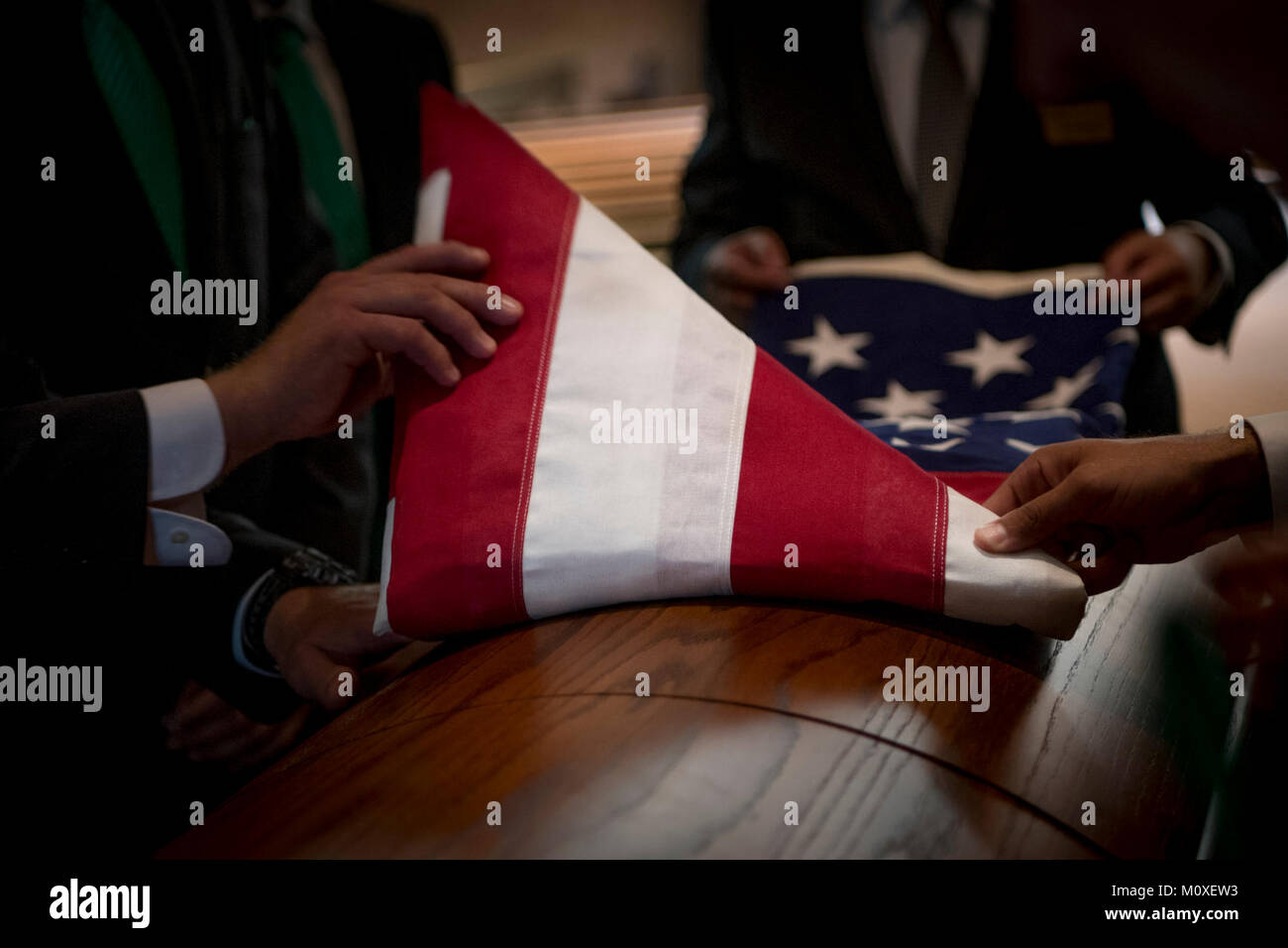 Individuals unfurl an American flag to drape on Special Warfare Operator 1st Class Patrick Jaeger's casket in St. - Stock Image