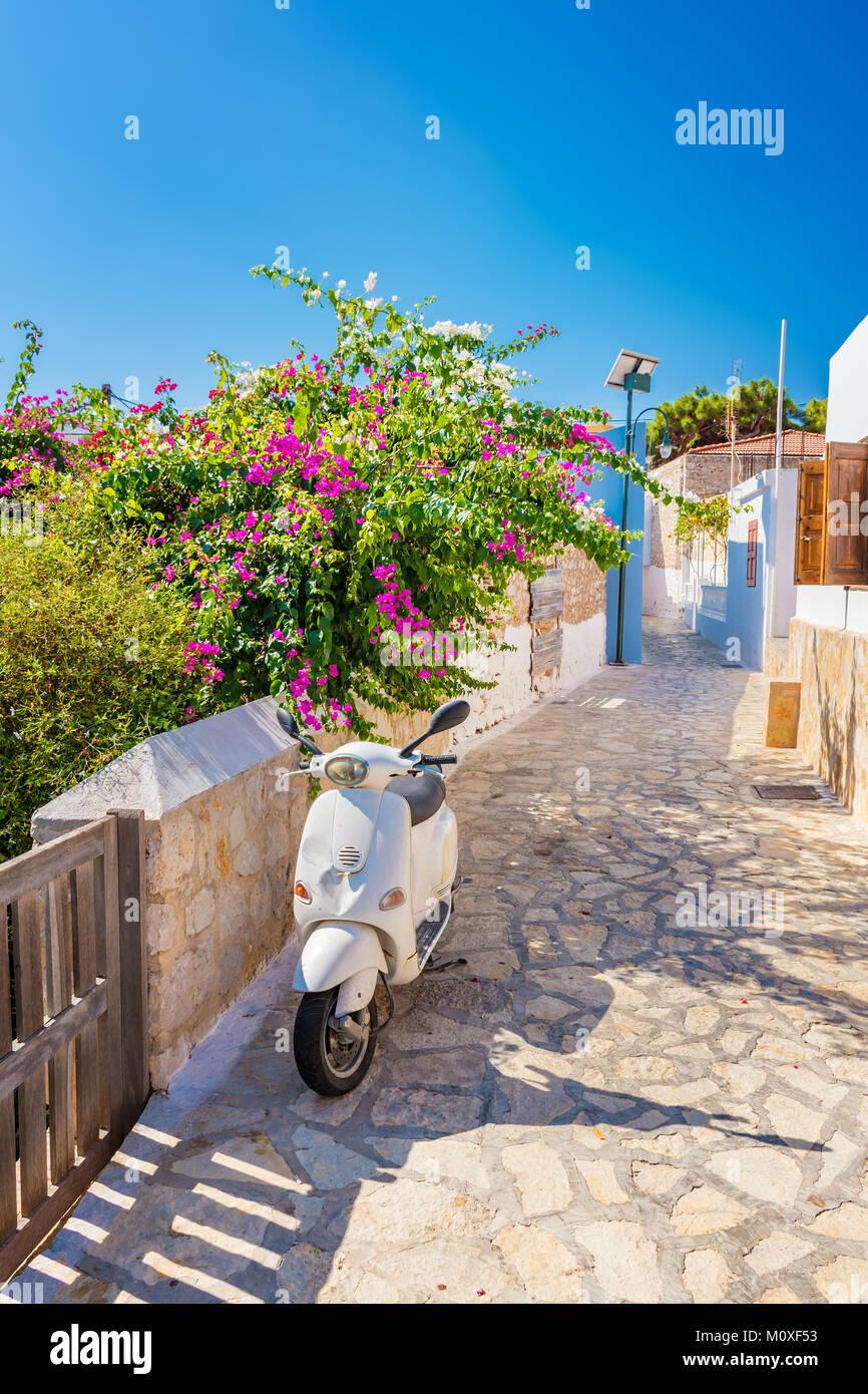 Scooter and flowers in Nimborio on island of Halki (Greece) - Stock Image