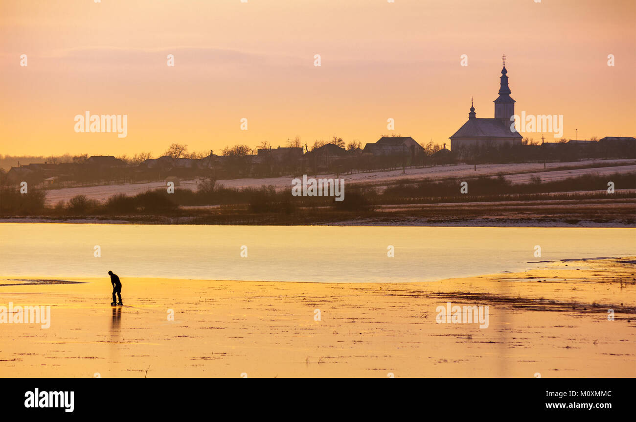undefined person skating on the frozen lake in evening. beautiful winter countryside scenery. village and church in a far distance Stock Photo