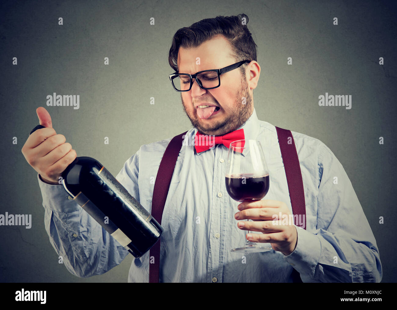 Man in bowtie trying wine and looking dissatisfied while exploring bottle. - Stock Image